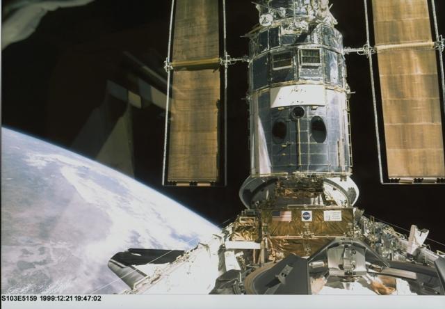 Hubble amarré à la navette américaine lors de la mission STS-103 en 1999. Crédits : NASA.